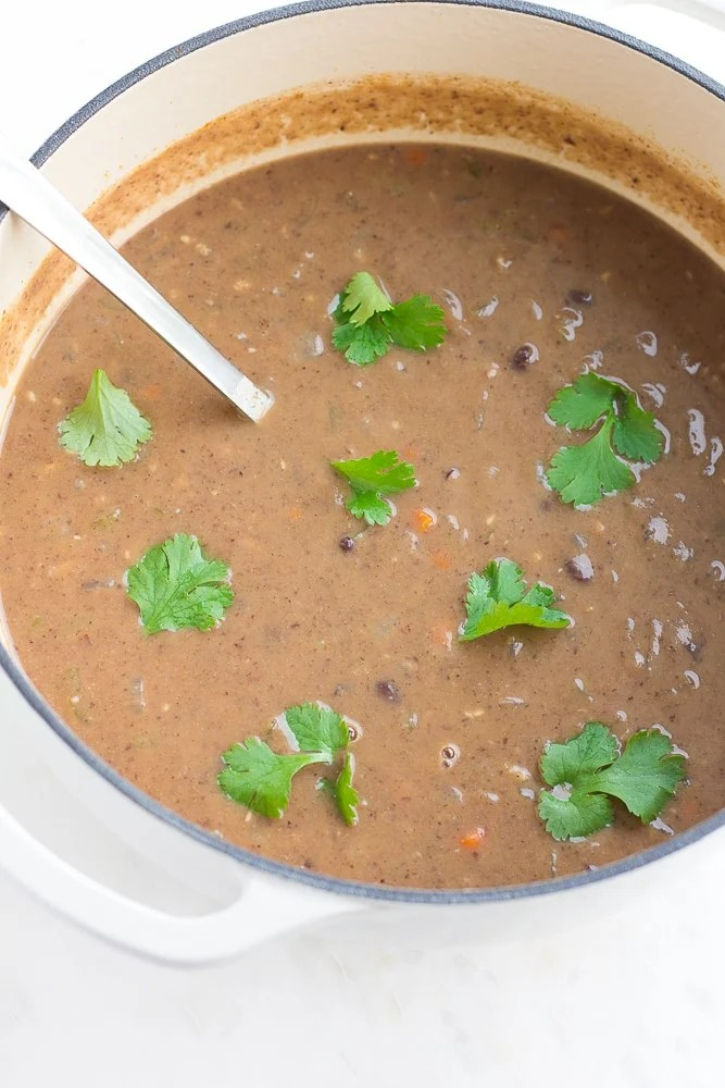 black bean soup in a large white pot with cilantro in it