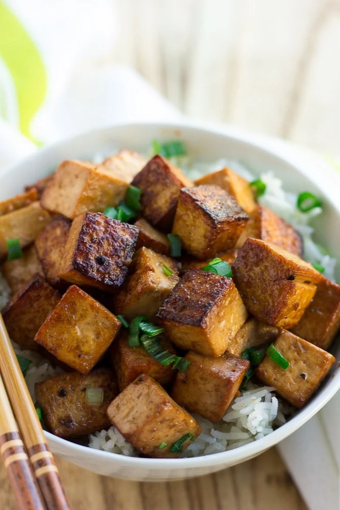 marinated tofu in a bowl with rice and green onions