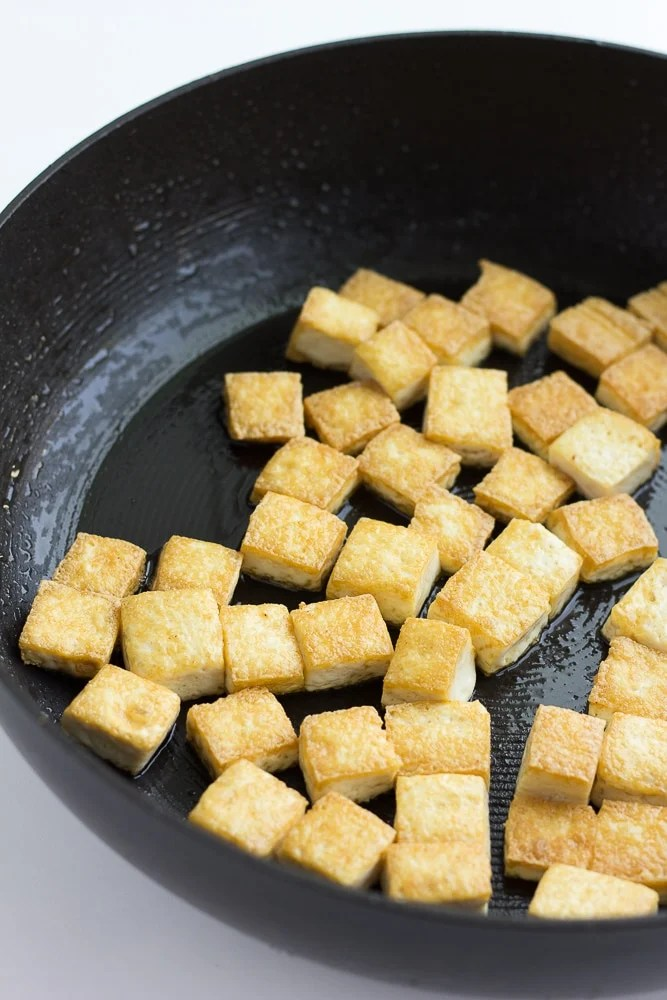 tofu frying in a large pan