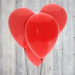 Red heart made of four balloons on light wood background