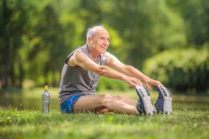 Joyful senior stretching his legs in a park