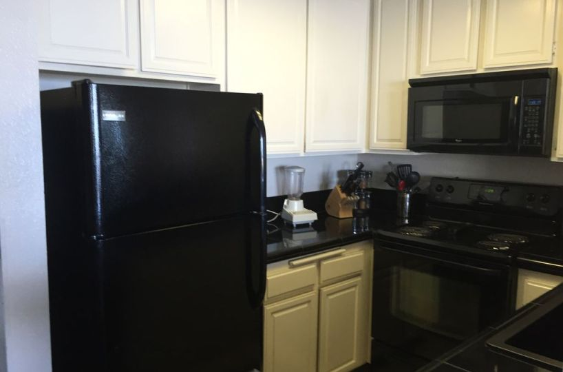 Black appliances and off white cabinets with black countertops