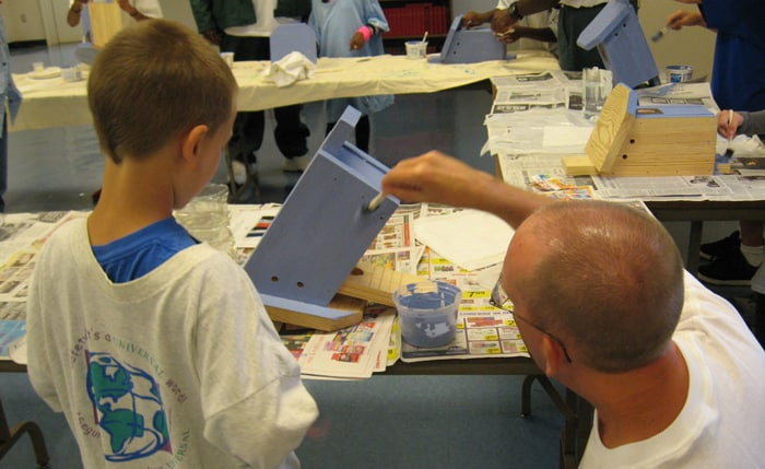 Marshall Murray and his son paint a bluebird house.