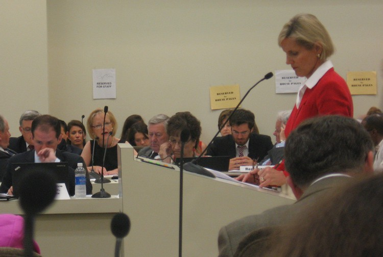 HHS Secretary Aldona Wos (far, blonde hair) speaks to legislative questions about HB 695. Rep. Ruth Samuelson (red jacket) stands in the foreground.
