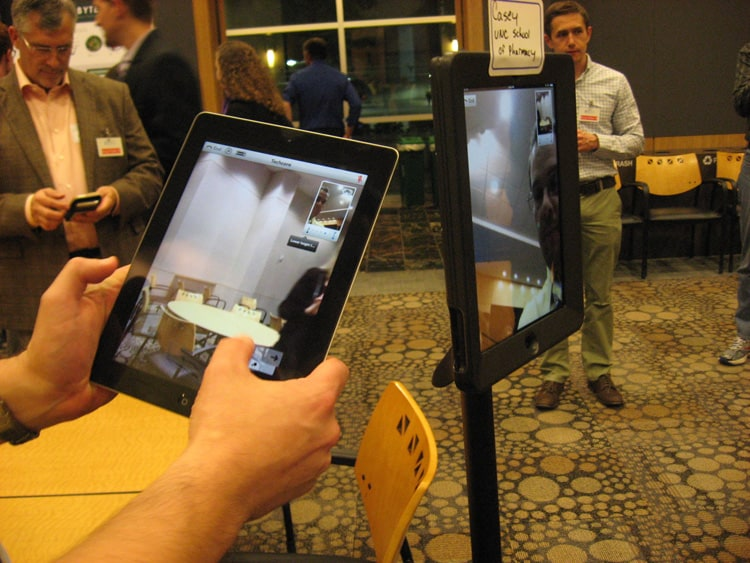 """Casey Emerson from the School of Pharmacy at UNC Chapel Hill demonstrates an """"iPad robot"""" that can facilitate video conferencing."""