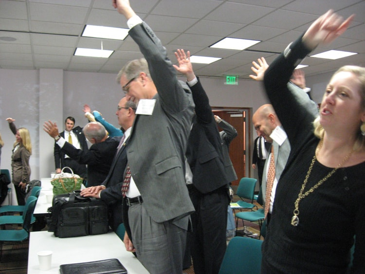 An employee from Prevention Partners lead meeting participants in an exercise break.