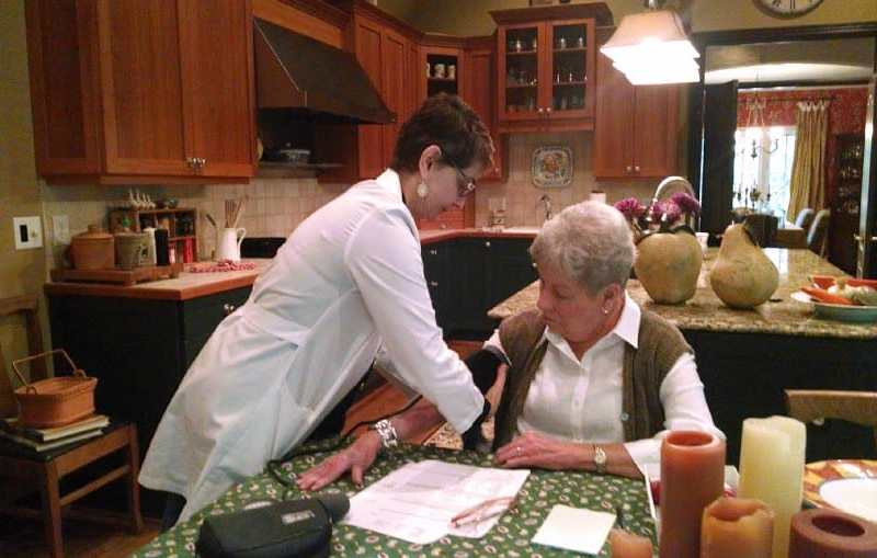 Dr. Taavoni checks Jerry Bell's blood pressure at her Chapel Hill home