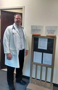 Brian Forrest, MD, stands in front of his fee chart in his Apex office. Prices include $29 for a sports physical and $64 for non-member exams.