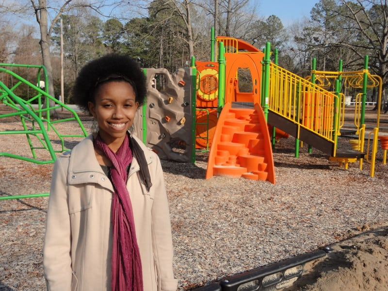 Victoria Chetty, a community transformation catalyst coordinator with the N.C. Public Health Foundation, stands in front of a Healthy Places NC-funded playground project.