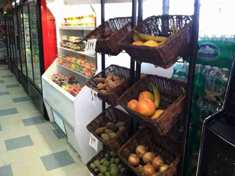 shows some produce on shelves in a corner store.