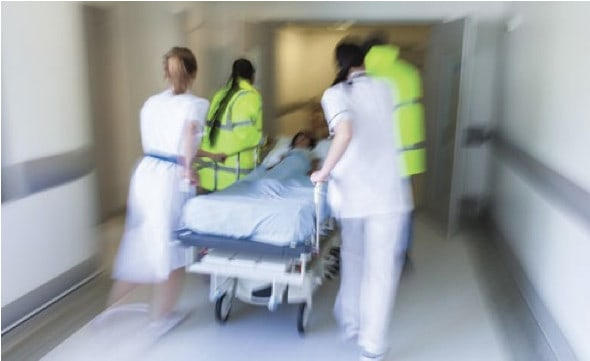 Often, patients who are readmitted after being sent home from the hospital return through the emergency room. Photo shows nurses rushing a patient on a gurney into a doorway.