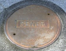 Picture of a sewer cover. A cover for a municipal sewer access point. Municipal sewer systems transport human waste from homes and businesses, and treat it in centralized wastewater plants. Photo courtesy Wikimedia Commons