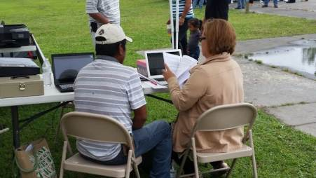 Farmworker Santos V. gets help reading a letter about his ACA insurance coverage from Ana Beltran, NC Farmworkers Project, Farmworker Educator.