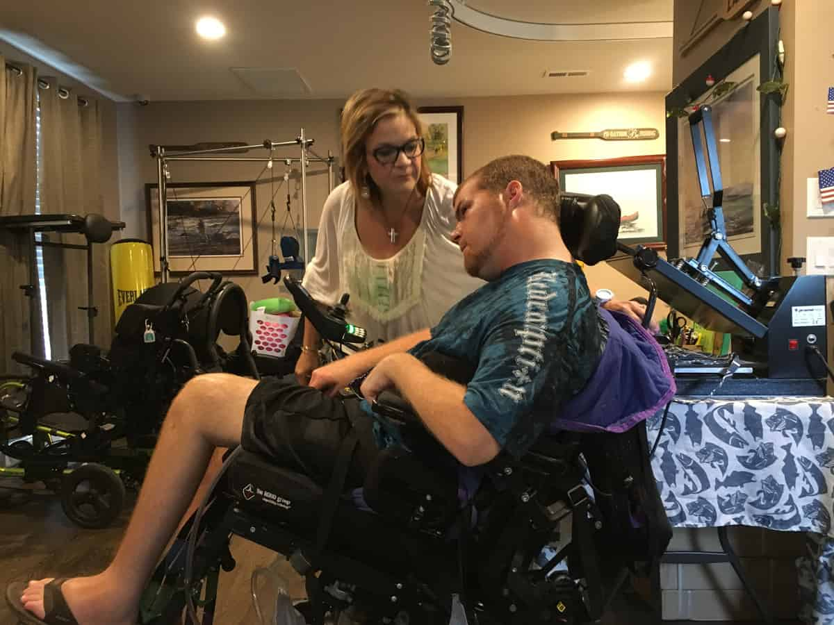 Jeannie Irby talks with son Zack, a traumatic brain injury survivor in his specially equipped room in the family home in Burlington.