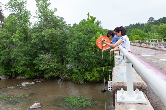 To lower sample bottles from a bridge, graduate students Catalina Lopez and Zachary Hopkins use a plastic cord dispenser, a long rope, and PVC pipe drilled with holes so it can sink to move a sample bottle into the Haw River and back up again. Photo by Julie Williams Dixon