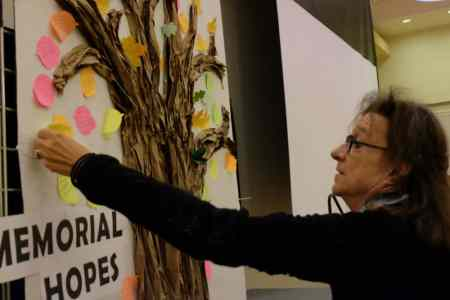 Karen Dunn, who runs Club Nova, a program for adults with severe and persistent mental illnesses in Carrboro, puts up a note with her hope for a Dix memorial on an art installation at the Lives on the Hill event Sunday at the Talley Student Union on the NC State University campus.