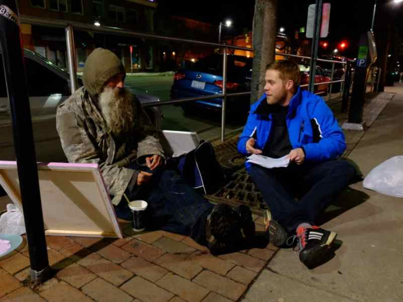 UNC Chapel Hill social work student Pat Hecker chats with a homeless man on Chapel Hill's Franklin St. during the 2016 Point In Time survey of homeless North Carolinians.