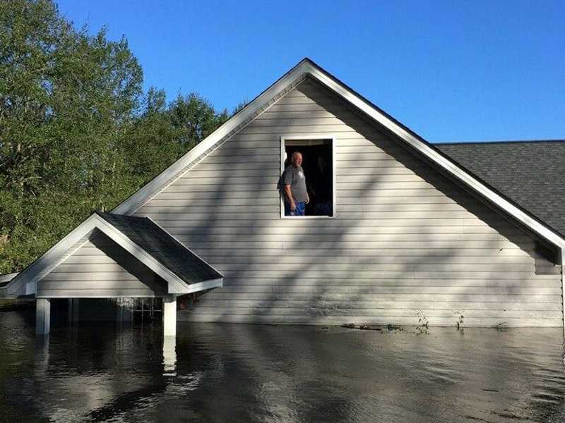 Shows man in an attic window. Flood waters come to about 5 feet below the window sill, completely covering the first floor.
