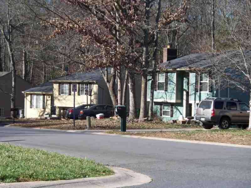 photo shows an average suburban street with houses and cars parked in front of them.