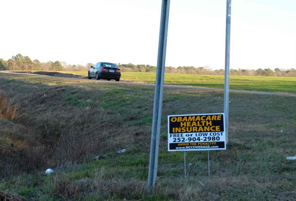 Sign at a lonely crossroads encouraging enrollment in Obamacare insurance