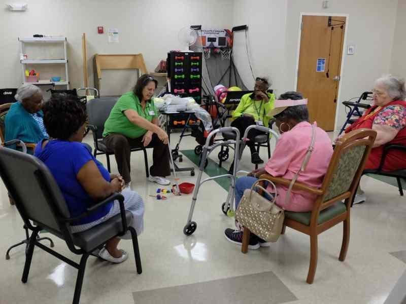 photo shows a group of elderly women sitting in a circle, being instructed by the OT who is using a grabber to pick up a toy from the floor
