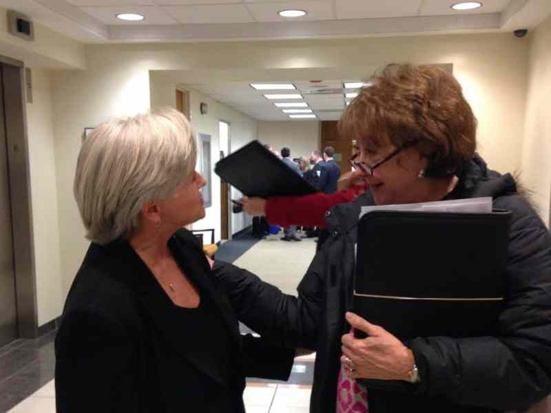 two women talking animatedly in a hallway near a bank of elevators