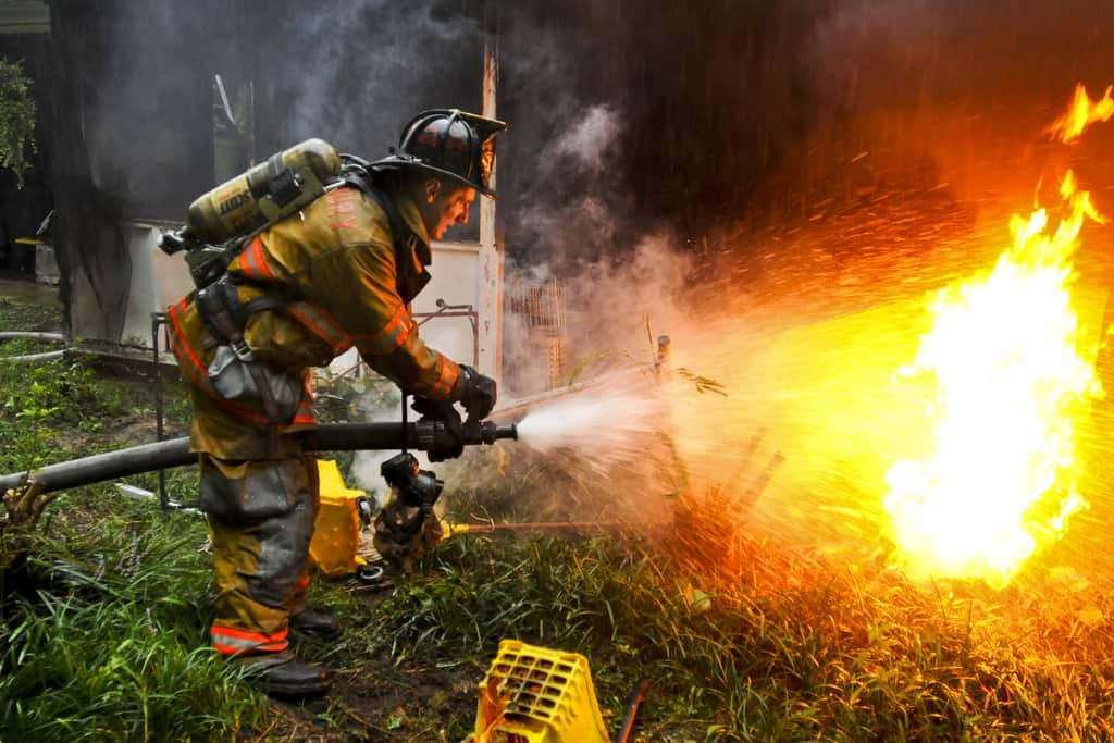 Army Pvt. 1st Class Lucas Ternell, a volunteer firefighter, and a member of the 20th Military Police Company, Maryland National Guard, puts out a small debis fire in the yard of a house fire in Salisbury, Md., Aug. 27. Ternell was aboard Rescue 16, which was one of several fire and rescue engines that reported to the fire inside a residential neighborhood. Guard members and civilian first responders are providing area support during the Hurricane Irene response. U.S. Army photo by Sgt. Darron Salzer