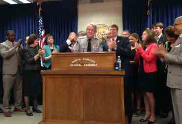 large group of people standing behind Harrison, who is at the podium.