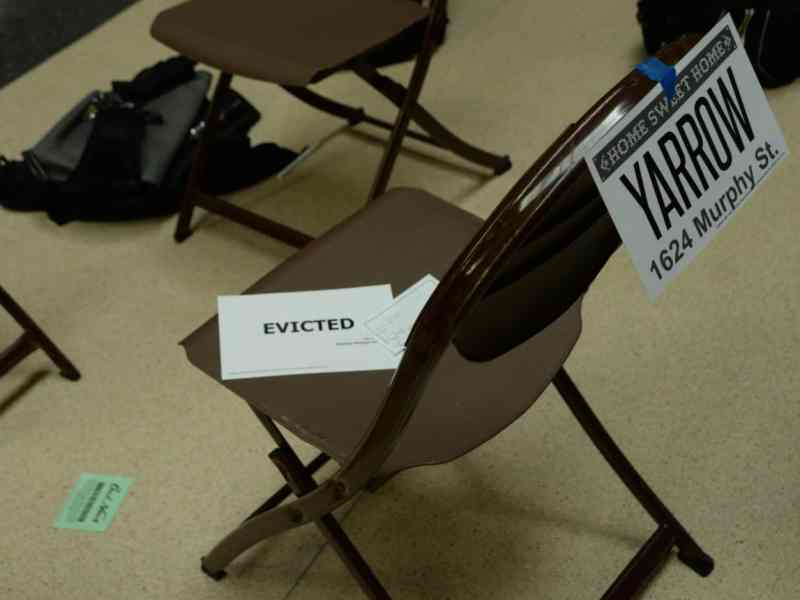"""A folding chair has an addres taped to the back and on the seat is a card labeled """"eviction"""""""