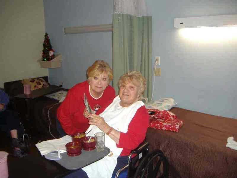 shows a woman bending down next to her mother, who sits in a chair, they're both smiling at the camera.