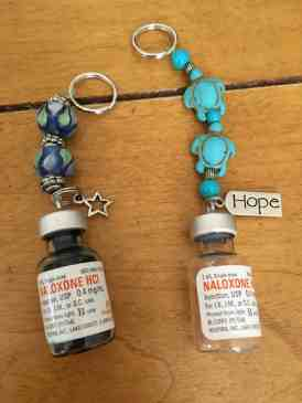 shows two keychains made from naloxine vials that are decorated with beads