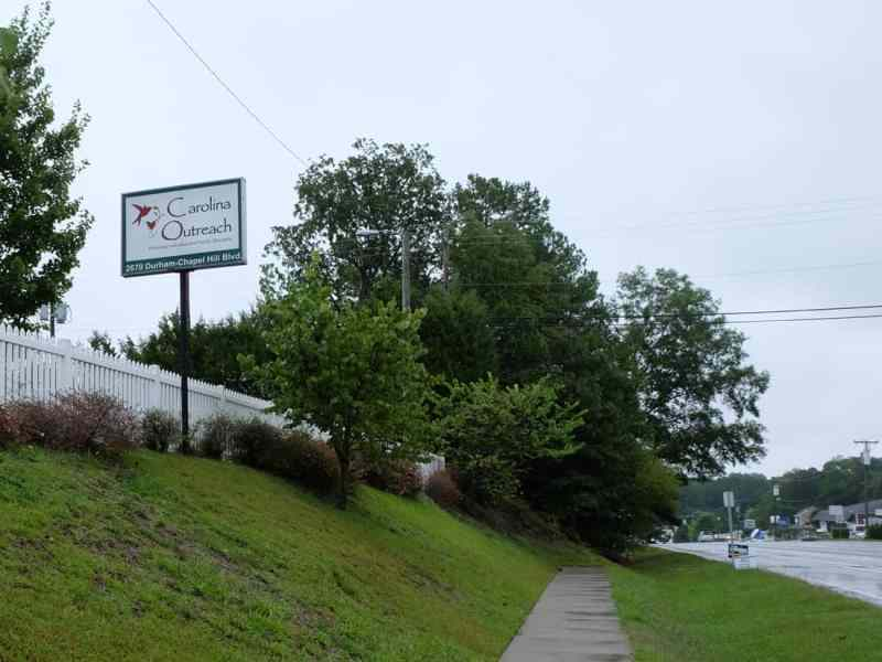 shows the sidewalk with Carolina Outreach (behavioral health urgent care) sign above