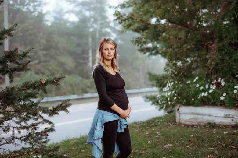 shows a visibly pregnant woman standing on a grassy field surrounded by trees