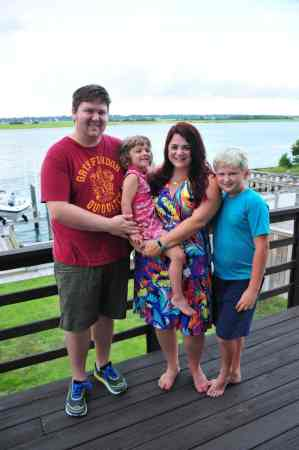 shows a mother, father and two children smiling at the camera. they look like they're at the coast, standing on a deck near the water.