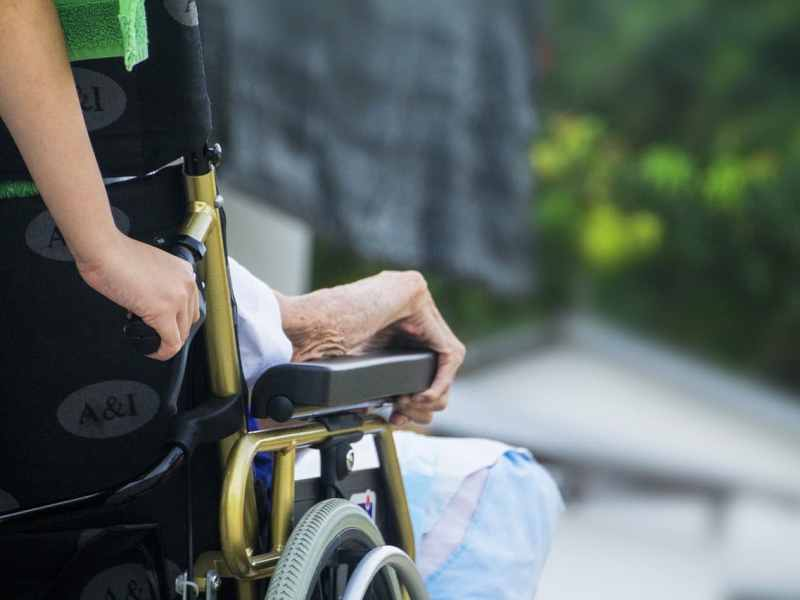 shows the back of a wheelchair, with an old and wizened hand on the arm of the chair
