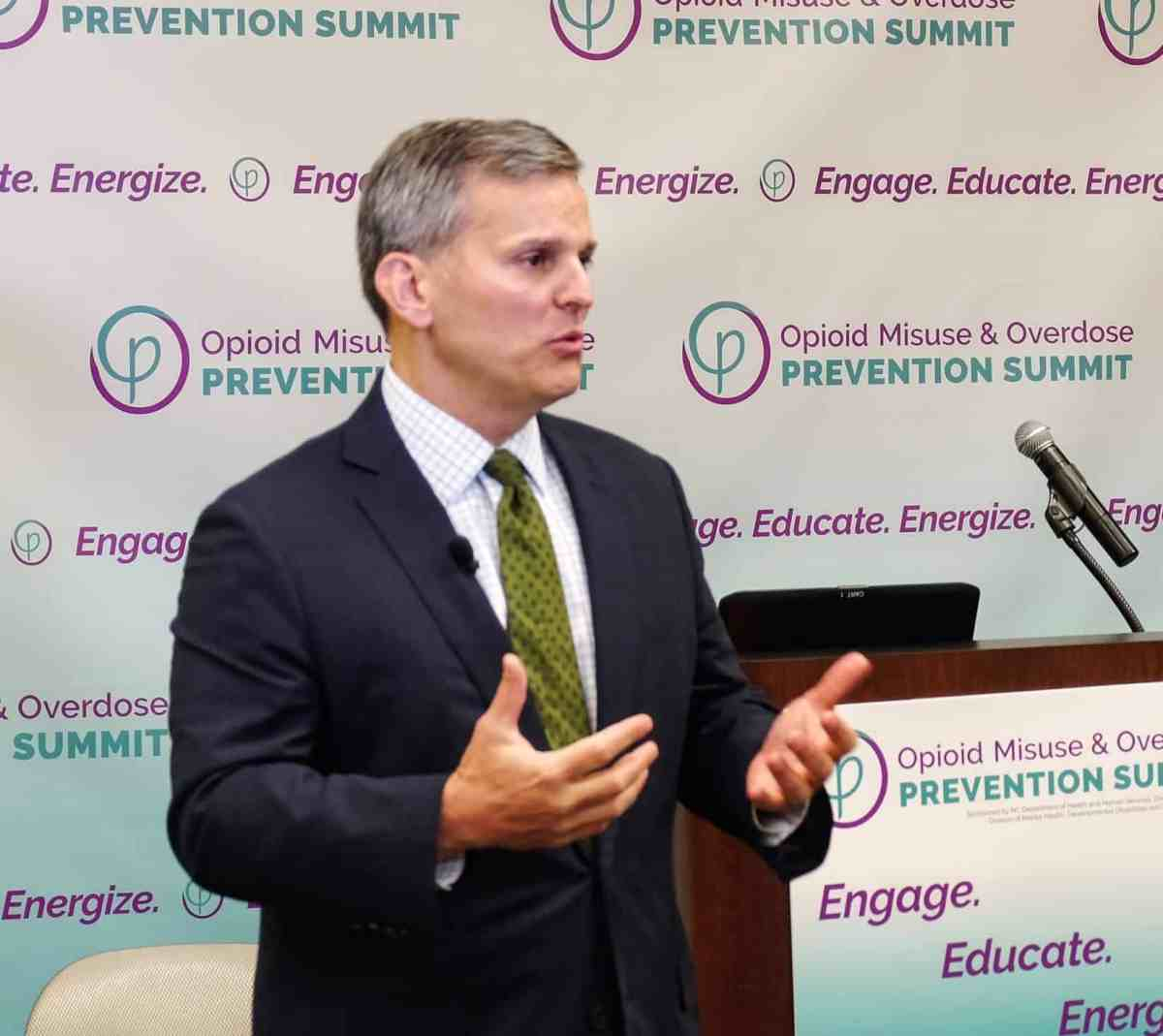 man stands by a podium, gesturing with his hands, speaking to an unseen audience at the opioid summit