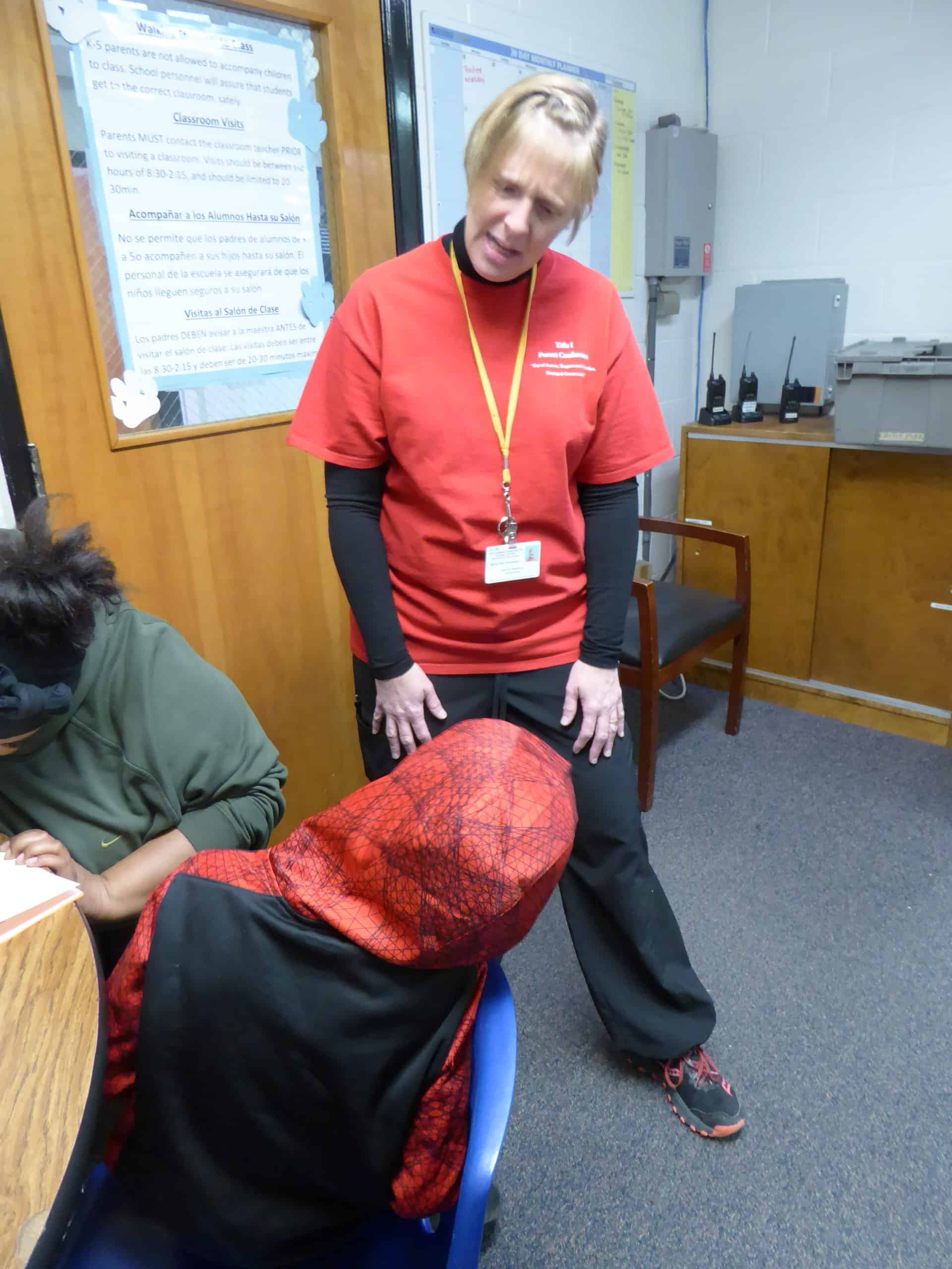 the school nurse talks to a little boy, while his mother sits at the adjacent table, filling out paperwork