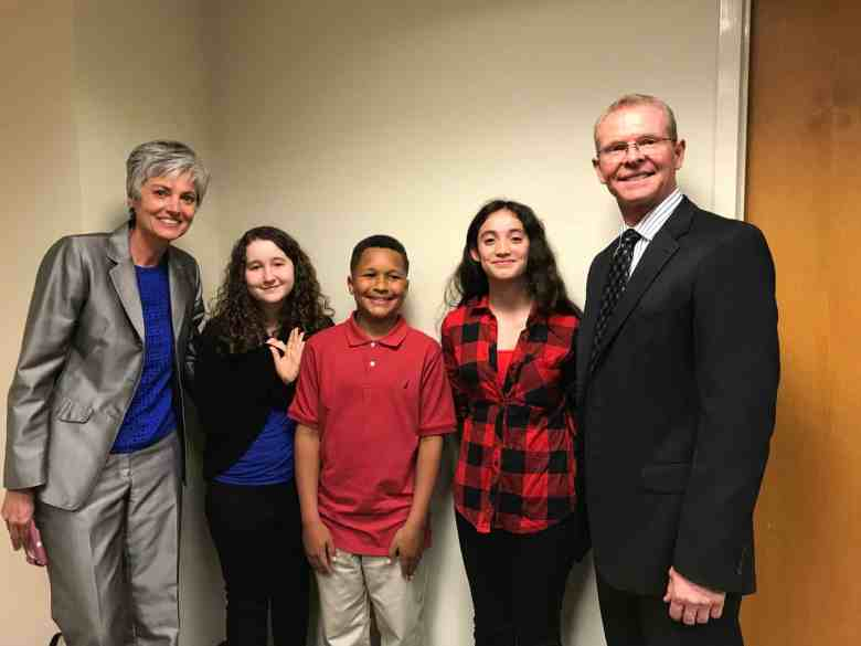shows a group of two adults flanking three children, two girls and a boy. they came to the legislature to discuss school safety, peer counseling