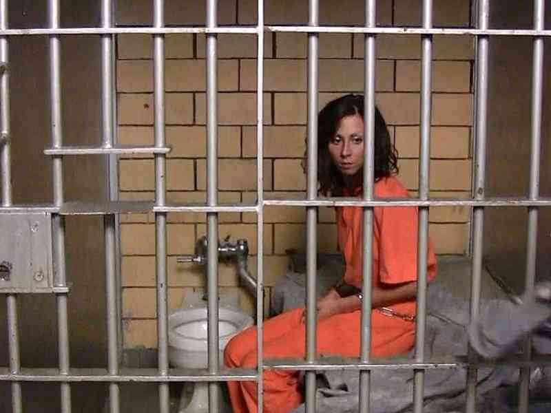 shows a woman in an orange jumpsuit, sitting on a bed, shackled. she's in a cell that has a sink and toilet.