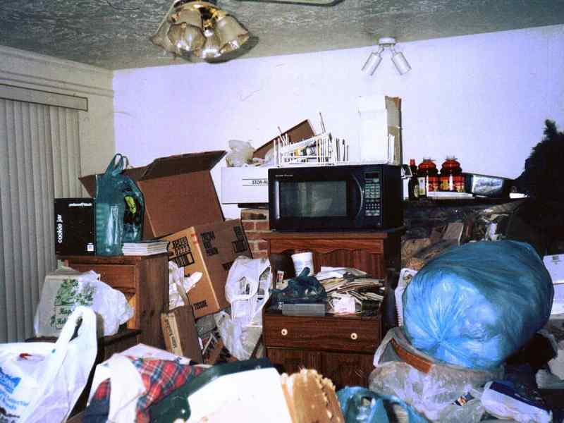 shows a living room cluttered with possessions, in some places piled up to the ceiling.
