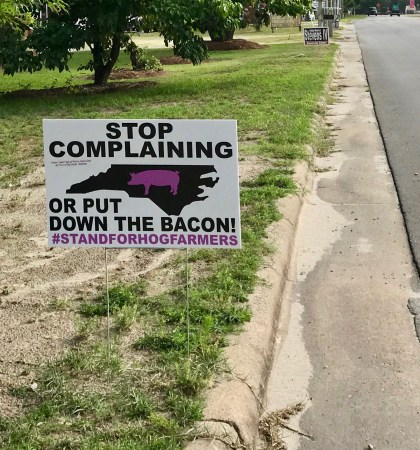 photo of a roadside sign that reads: STop complaining or put down the bacon