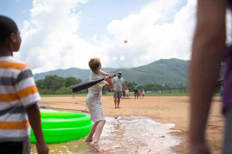 shows a boy swinging at a ball with a bat, he lives in a foster care group home