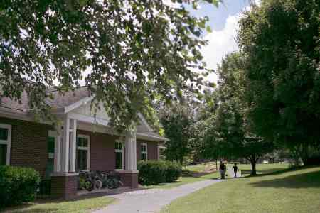 shows a bjilding with a path in front. A group of bicycles are parked in front of the building which is part of a foster care group home.