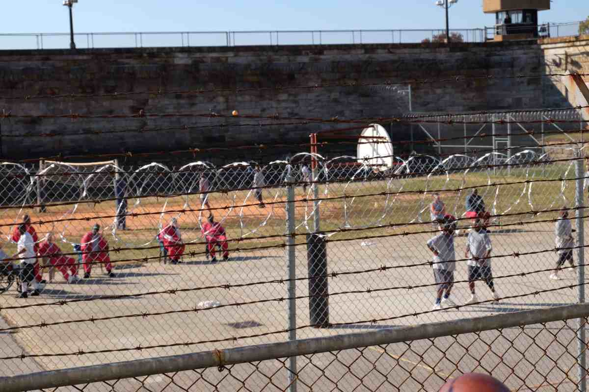 a fence is in the foreground, with a dozen men in jumpsuits beyond it, they're sitting on benches and seveal are playing basketball. More inmates with mental illness find themselves in solitary confinement following the 2017 deaths of prison officers in NC.