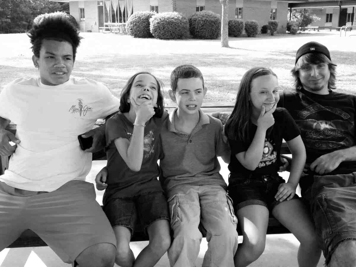 shows five children sitting on a bench, most of them are smiling at the camera.