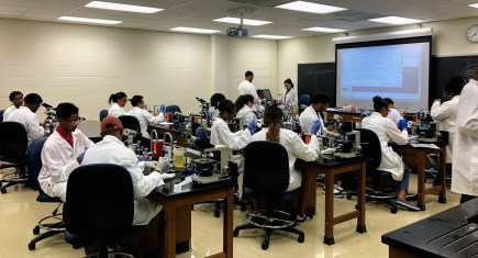 a group of students of color in lab coats and safety goggles in a lab