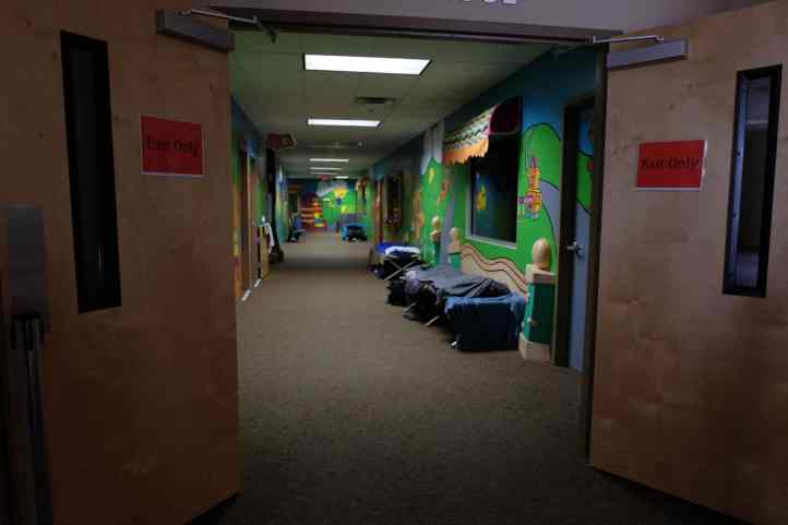 shows several cots sitting in a brightly painted hallway