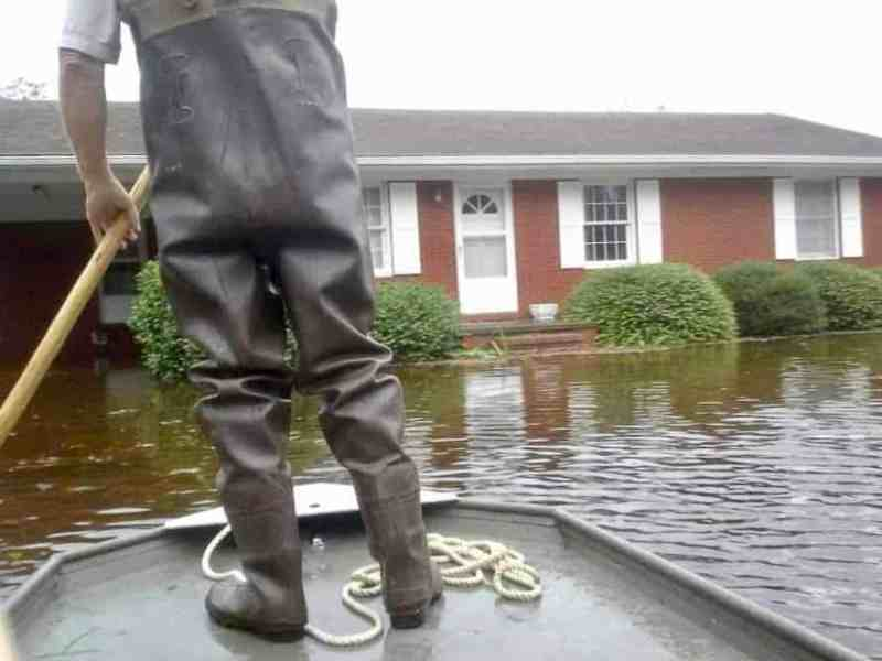 We see a house that has floodwaters up to the threshold of the front door. the photo is taken from on a boat, we can see the bow of the boat and a man in bib waders with his back to the camera. Took place during Hurricane Florence. standing on the bow holding a rope.