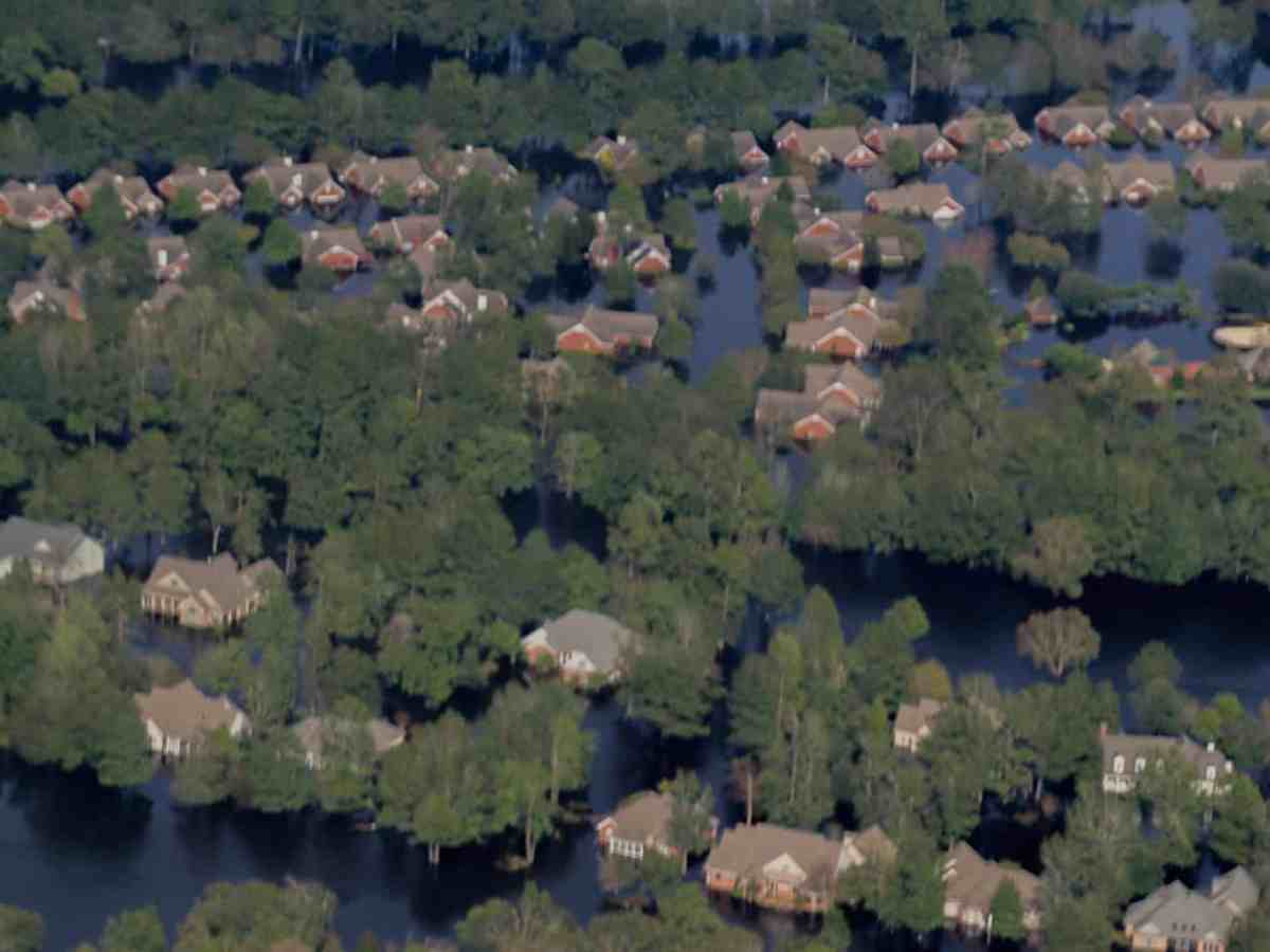Shows a suburban neighborhood of upscale homes, each surrounded by water.