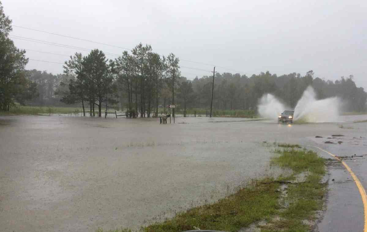 shows a flooded road with someone driving into the water at a fast pace